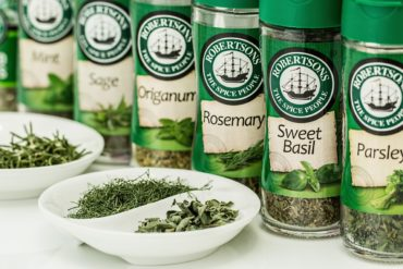Dried herbs in glass jars from a spice rack